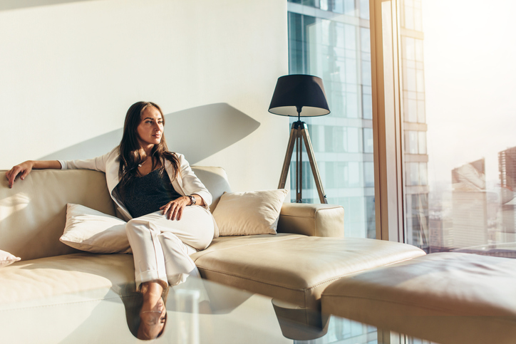 Portrait of successful businesswoman wearing elegant formal suit sitting on leather sofa relaxing after work at home